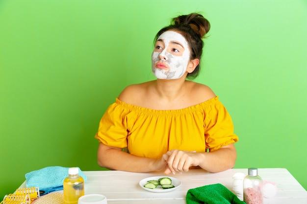 Porträt der jungen kaukasischen frau in ihrem schönheitstag, haut- und haarpflege-routine. weibliches modell mit naturkosmetik, die gesichtsmaske für make-up anwendet. körper- und gesichtspflege, natürliches schönheitskonzept.