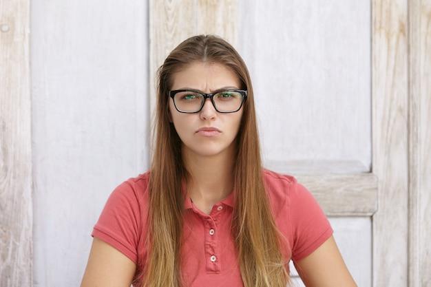 Porträt der jungen kaukasischen frau mit dem langen losen haar, das stilvolle brille und poloshirt trägt, die verärgertes und unglückliches aussehen haben, stirnrunzeln und schiefes gesicht machen, gegen holzwand sitzen