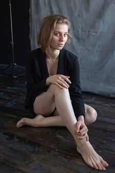 Porträt der jungen kaukasischen frau mit den kurzen haaren in der schwarzen anzugjacke, die auf boden sitzt. modellversuche von hübschen mädchen