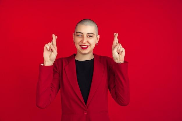 Porträt der jungen kaukasischen frau mit glatze auf roter wand red