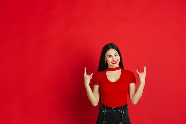 Porträt der jungen kaukasischen frau mit hellen emotionen auf rotem studiohintergrund