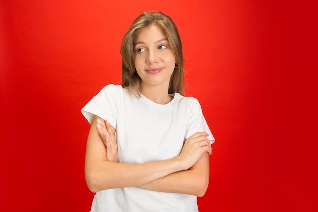 Porträt der jungen kaukasischen frau mit hellen gefühlen auf rotem studio