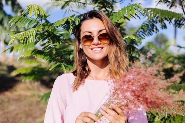 Porträt der jungen kaukasischen gebräunten frau im romantischen rosa kleid runde ohrringe silberarmband und sonnenbrille mit wilden blumen