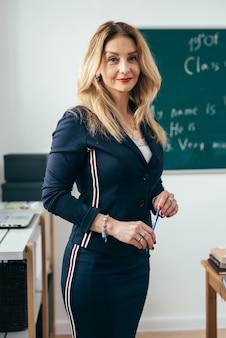 Porträt der jungen kaukasischen lehrerin im klassenzimmer.