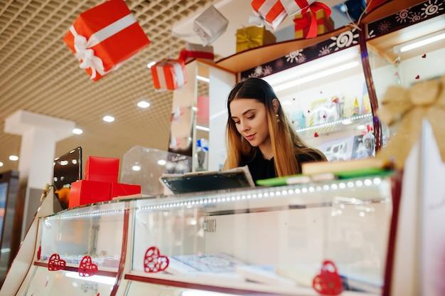 Porträt der jungen kaukasischen weiblichen verkäuferin beachten etwas. kleines geschäft von süßigkeiten souvenirs shop.