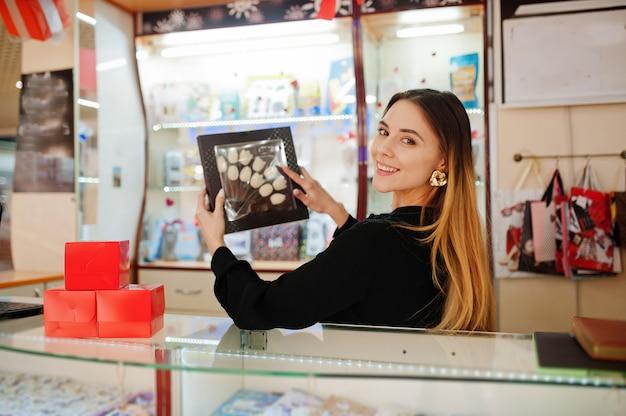 Porträt der jungen kaukasischen weiblichen verkäuferin halten schachtel mit schokoladentulpen. kleines geschäft von süßigkeiten souvenirs shop.