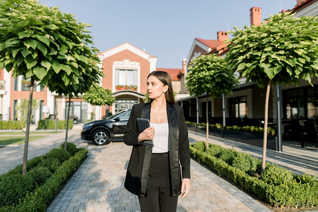 Porträt der jungen kaukasischen ziemlich konzentrierten geschäftsfrau, die mit digitalem tablett gegen schwarzes auto und modernes bürozentrum im freien geht