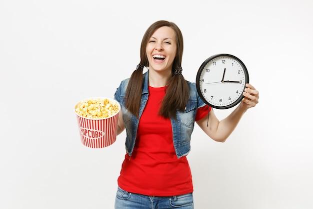 Porträt der jungen lachenden attraktiven brünetten frau in freizeitkleidung, die filmfilm ansieht, eimer popcorn und runden wecker einzeln auf weißem hintergrund hält. emotionen im kinokonzept.