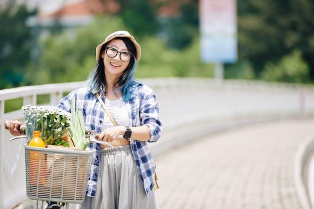 Porträt der jungen lächelnden asiatischen frau, die entlang der straße mit fahrrad geht. der korb ist voller lebensmittel und blumen