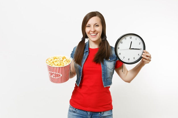 Porträt der jungen lächelnden attraktiven brünetten frau in der freizeitkleidung, die filmfilm ansieht, eimer popcorn und runden wecker einzeln auf weißem hintergrund haltend. emotionen im kinokonzept.