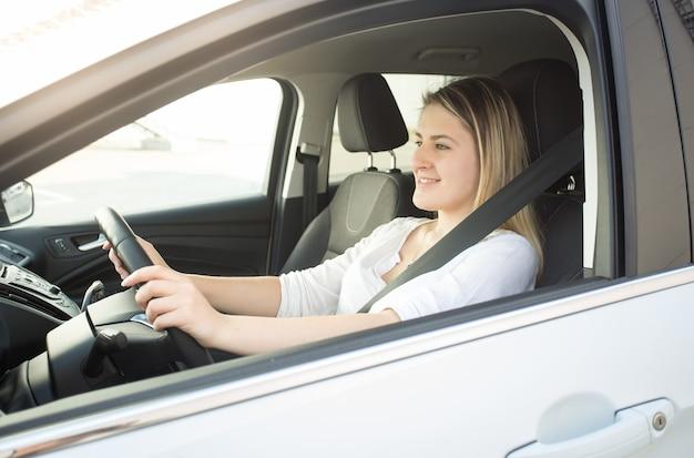 Porträt der jungen lächelnden frau, die auto fährt und straße betrachtet