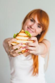 Porträt der jungen lächelnden frau, die gegrilltes sandwich gegen weißen hintergrund darstellt