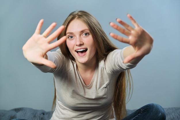 Porträt der jungen lächelnden frau, die ihre arme winkt und mit den händen gestikuliert hallo, hallo, auf wiedersehen