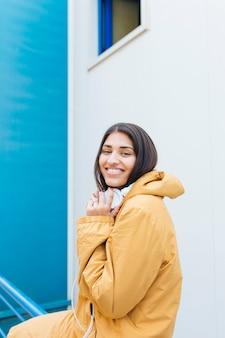 Porträt der jungen lächelnden frau, die kopfhörer auf ihrem hals hält