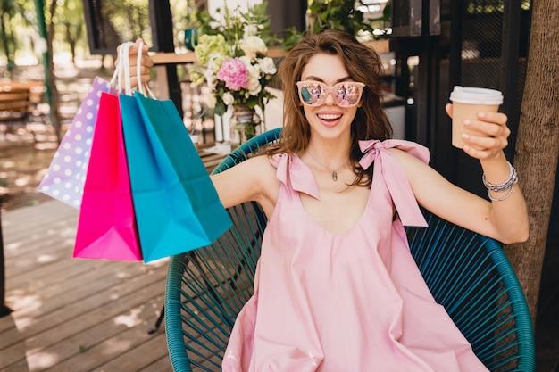 Porträt der jungen lächelnden glücklichen hübschen frau mit aufgeregtem gesichtsausdruck, der im café mit einkaufstüten sitzt, die kaffee, sommermode-outfit, rosa baumwollkleid, trendige kleidung trinken