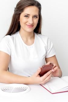 Porträt der jungen lächelnden kosmetikerin mit smatphone im schönheitssalon