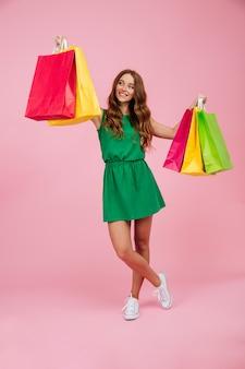 Porträt der jungen lächelnden lesekopffrau im grünen kleid, das bunte einkaufstaschen hält