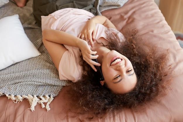 Porträt der jungen lächelnden niedlichen jungen afroamerikanerin, die auf dem bett in ihrem zimmer liegt und mit freund am telefon spricht.