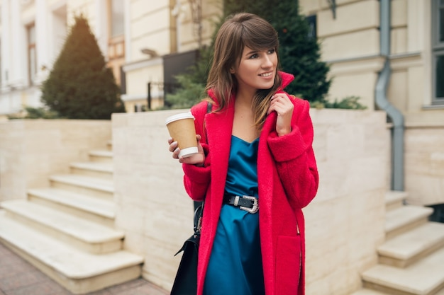 Porträt der jungen lächelnden schönen stilvollen frau, die in der stadtstraße im roten mantel geht, der kaffee trinkt