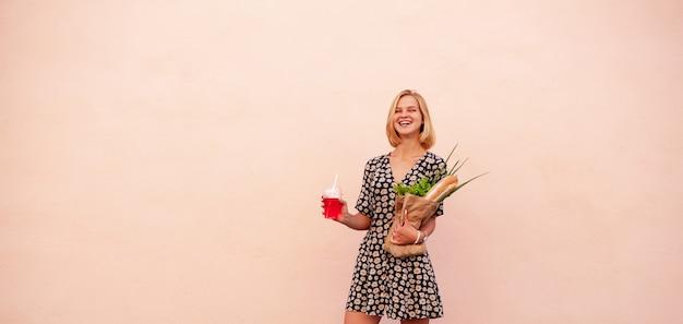 Porträt der jungen lächelnden studentenfrau mit handwerksshoptasche, mit grünem salat, zwiebel und brot. gesundes essen