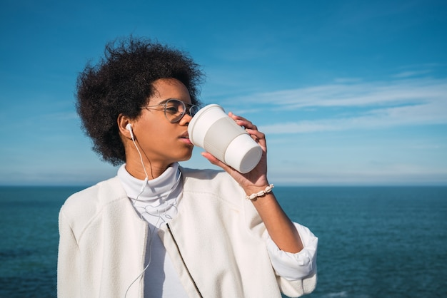 Porträt der jungen lateinamerikanischen frau, die eine tasse kaffee trinkt, während musik mit kopfhörern mit dem meer auf hört. musik, lebensstil.