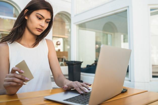 Porträt der jungen lateinamerikanischen frau, die kreditkarte hält und laptop verwendet, um online in einem café einzukaufen. online-shopping und lifestyle-konzept.