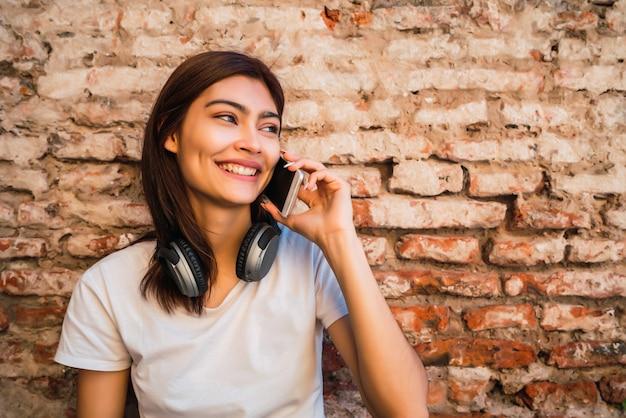 Porträt der jungen lateinischen frau, die am telefon draußen gegen backsteinmauer spricht. stadt- und kommunikationskonzept.