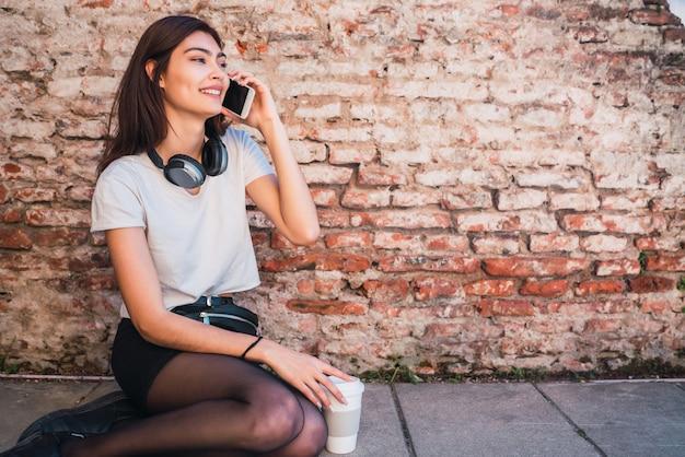 Porträt der jungen lateinischen frau, die am telefon spricht, während draußen im freien gegen backsteinmauer sitzt. stadtkonzept.