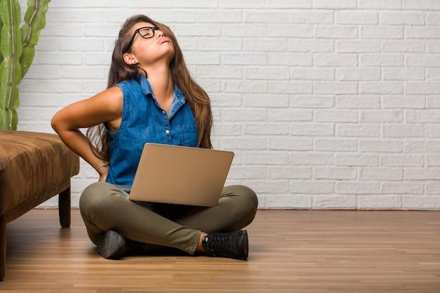 Porträt der jungen lateinischen frau, die auf dem boden mit den rückseitigen schmerz wegen des arbeitsstresses sitzt