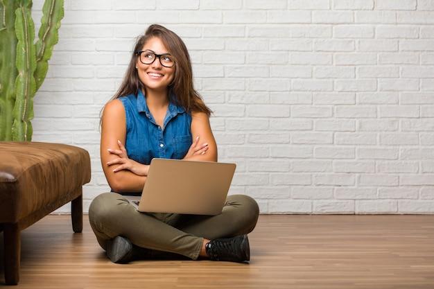 Porträt der jungen lateinischen frau, die auf dem boden oben schaut, an etwas spaß denkend sitzt und eine idee, ein konzept der fantasie, glücklich und aufgeregt hat. einen laptop halten.