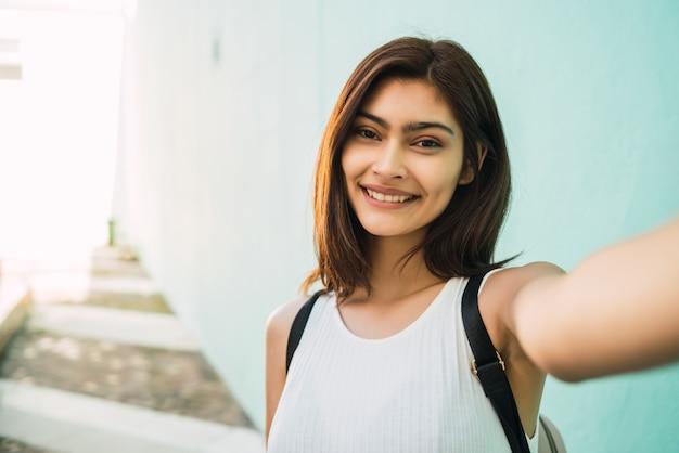 Porträt der jungen lateinischen frau, die ein selfie draußen in der straße nimmt. lifestyle und stadtkonzept.