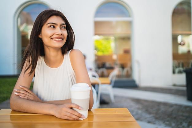 Porträt der jungen lateinischen frau, die eine tasse kaffee draußen am kaffeehaus genießt und trinkt. lifestyle-konzept.