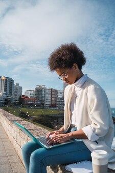 Porträt der jungen lateinischen frau, die ihren laptop benutzt, während sie draußen auf der straße sitzt. stadt- und technologiekonzept.