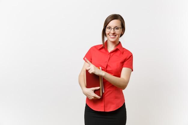 Porträt der jungen lehrerfrau im roten hemd, im rock und in den gläsern, die bücher halten, finger beiseite auf den kopienraum zeigend, der auf weißem hintergrund lokalisiert wird. bildung oder lehre im hochschulkonzept