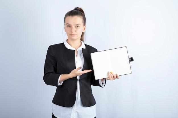 Porträt der jungen lehrerin, die auf ihr notizbuch auf weißem hintergrund zeigt. hochwertiges foto