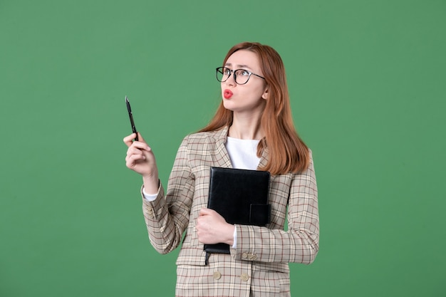 Porträt der jungen lehrerin im anzug mit notizblock auf grün