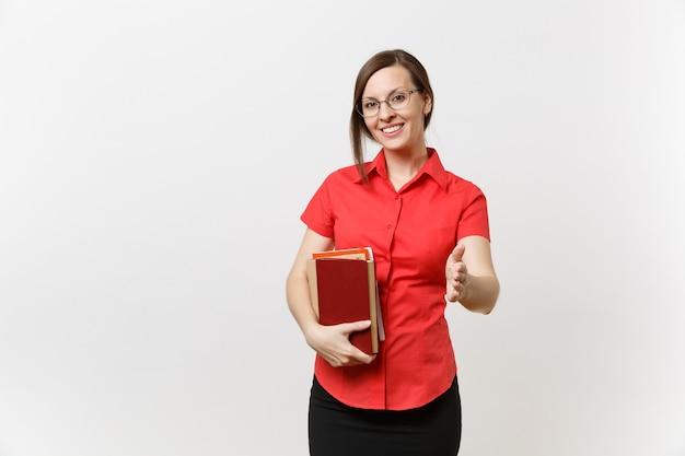 Porträt der jungen lehrerin in roten hemdrockgläsern halten bücher, stehen mit ausgestreckter hand zum gruß isoliert auf weißem hintergrund. bildung oder lehre im hochschulkonzept.
