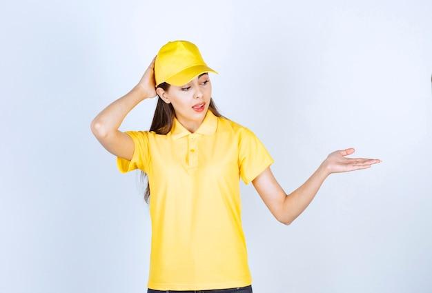 Porträt der jungen lieferfrau in der gelben kappe, die auf weiß steht.