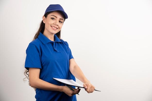 Porträt der jungen lieferungsfrau mit klemmbrett. foto in hoher qualität