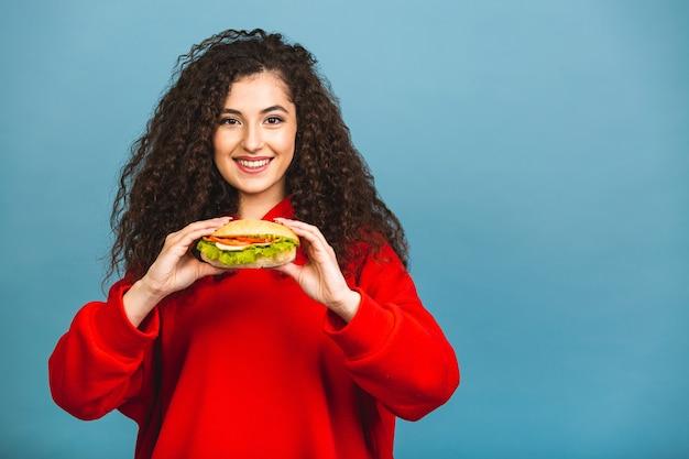 Porträt der jungen lockigen schönen hungrigen frau, die burger isst. isoliertes porträt des studenten mit fast food über blauem hintergrund.