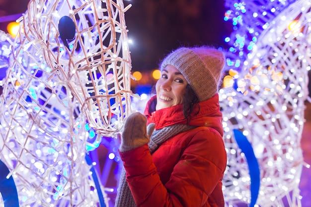 Porträt der jungen lustigen attraktiven frau über schneebedeckten weihnachtshintergrundwinterferien und -saison