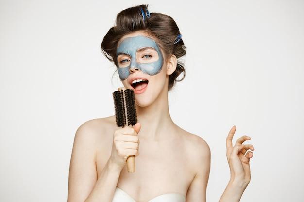 Porträt der jungen lustigen frau in den lockenwicklern und in der gesichtsmaske, die im kamm singt. schönheits- und hautpflegekonzept.