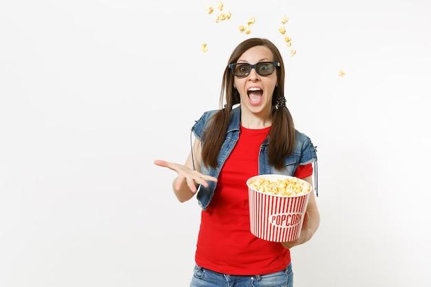 Porträt der jungen lustigen hübschen frau in 3d-brille, freizeitkleidung, die filmfilm ansieht, eimer popcorn hält, knallendes erbrechen, popcorn lokalisiert auf weißem hintergrund. emotionen im kinokonzept
