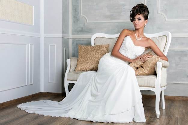 Porträt der jungen luxuriösen brünetten braut, die auf vintages sofa im schönen hochzeitskleid sitzt