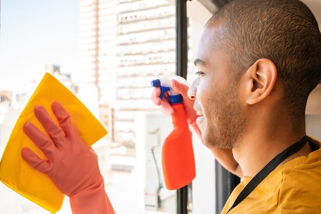 Porträt der jungen männlichen haushälterin, die glasfenster zu hause reinigt. reinigungs- und reinigungskonzept.
