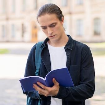 Porträt der jungen männlichen studentenlesung