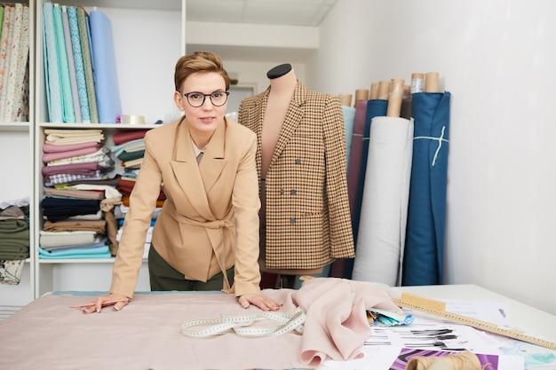 Porträt der jungen modedesignerin in brillen beim stehen nahe ihrem arbeitsplatz in der werkstatt