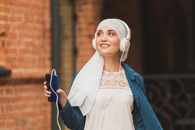 Porträt der jungen modernen arabischen frau, die handy hält und die musik zum kopfhörer hört.