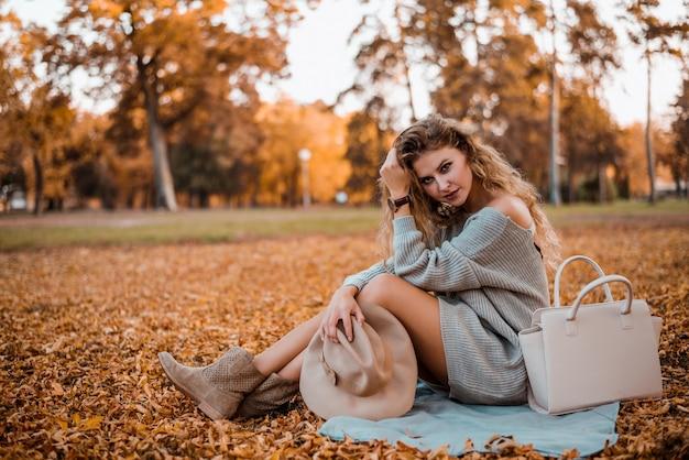 Porträt der jungen modernen frau, die im herbstpark sitzt.