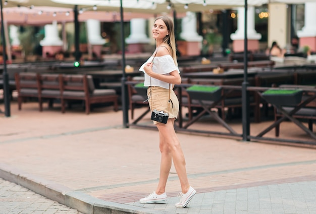 Porträt der jungen modischen frau in der modischen kleidung mit retro-kamera in der städtischen umgebung